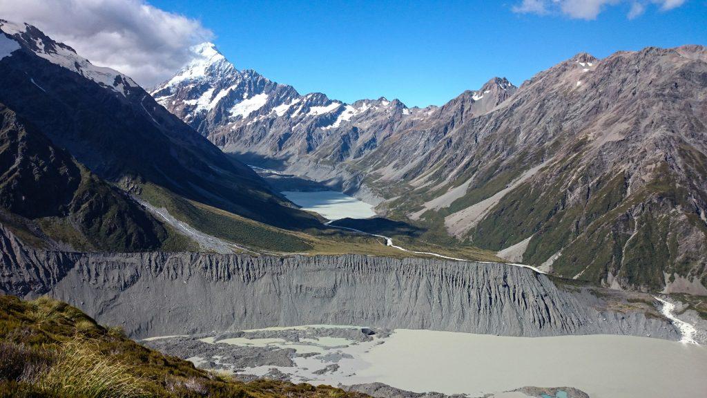 Wanderungen im Mount Cook Nationalpark, Aoraki, Südinsel Neuseeland, Wanderung zum Kea Point Track mit Sonnenschein, schneebedeckte Gipfel in der Ferne, raue, lebensfeindliche und doch wunderschöne Umgebung, Sonnenschein, schlammiges Gletscherwasser