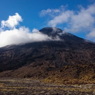 Tongariro Alpine Crossing Wanderung, Nordinsel Neuseeland, Vulkanlandschaft, lebensfeindliche Landschaft, in Wolken gehüllte Berge, Geröll und Steine, Vulkan Gipfel, mystisch