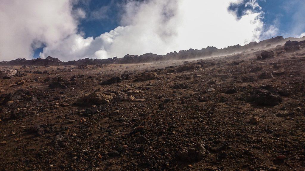 Tongariro Alpine Crossing Wanderung, Nordinsel Neuseeland, Vulkanlandschaft, lebensfeindliche Landschaft, in Wolken gehüllte Berge, Geröll und Steine