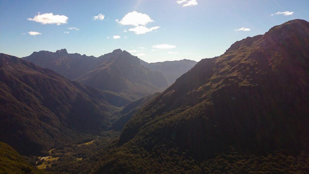 Wanderung Kepler Track - Great Walk, Wanderweg entlang Bergkamm im rauen Gelände, alpin oberhalb Baumgrenze, herrliche Aussicht auf umliegende Berge, herrlicher Sommertag in Neuseeland Südinsel, Fiordland National Park, Wandertag beim Kepler Track