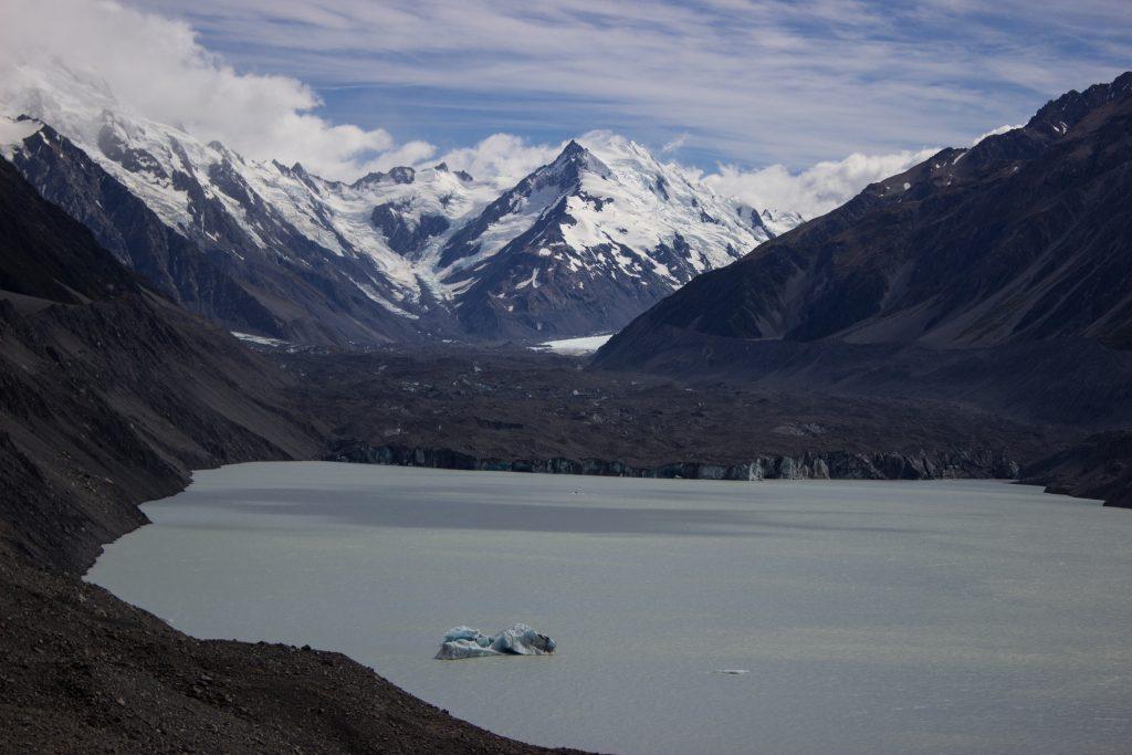 Wanderungen im Mount Cook Nationalpark, Aoraki, Südinsel Neuseeland, Wanderung zum Tasman Glacier View, schwimmender kleiner Eisberg im Gletschersee, schneebedeckte Gipfel in der Ferne, raue, lebensfeindliche und doch wunderschöne Umgebung