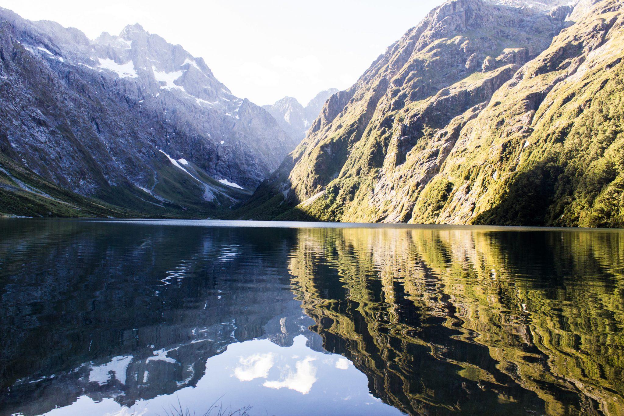 Lake Marian Track wandern, bei Marian Falls im Fiordland National Park Südinsel Neuseelands, Wanderung zum See Marian, Lake Marian, Tal, hanging valley, schneebedeckte Gipfel in der Ferne, Berge spiegeln sich im klaren Wasser, schönes Licht, Sonne, Steine
