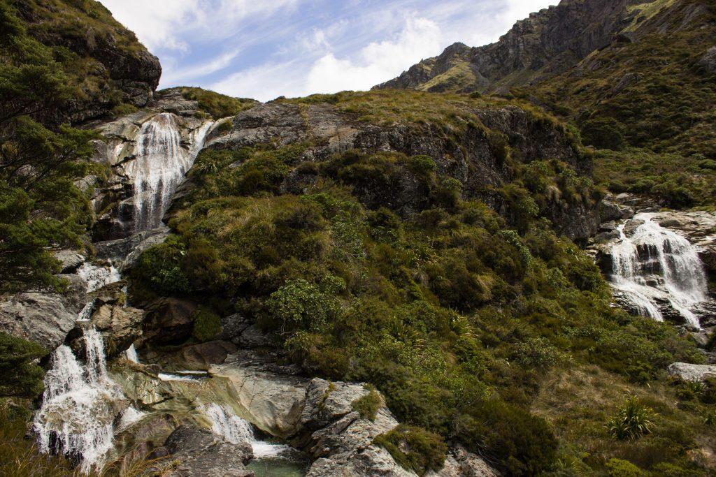 Wanderung Routeburn Track - Great Walk im Fiordland Nationalpark Südinsel Neuseeland, Wanderweg Routeburn im Fiordland Nationalpark, beeindruckende Berge mit schneebedeckten Gipfeln über der Baumgrenze, herrlicher Sommertag auf Südinsel Neuseelands, traumhafte Wanderung, raues Gebirgsklima, lebensfeindlich und doch wunderschön, beeindruckend, Wasserfall
