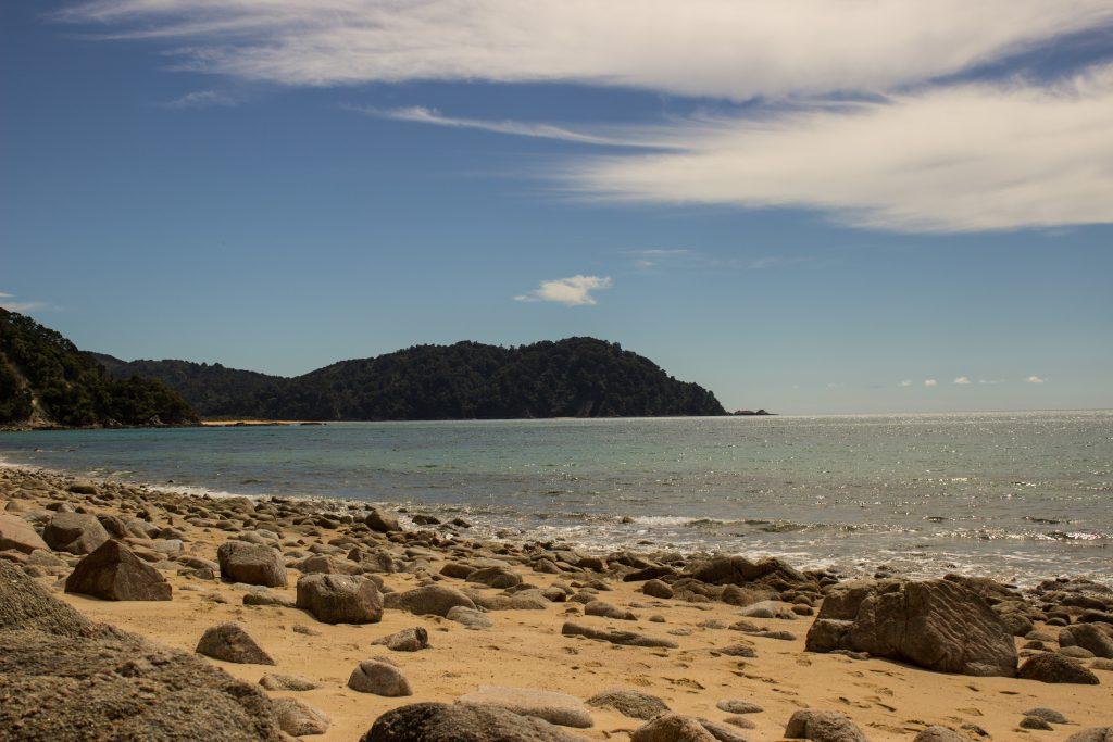 Wanderung Abel Tasman Coast Track Great Walk Südinsel Neuseeland, Aussicht auf traumhafte, sichelförmige Bucht mit blaugrünem klarem frischem Wasser und dichtem grünem Wald, Sonnenschein, Palmen und Farne, goldener Sandstrand mit Steine