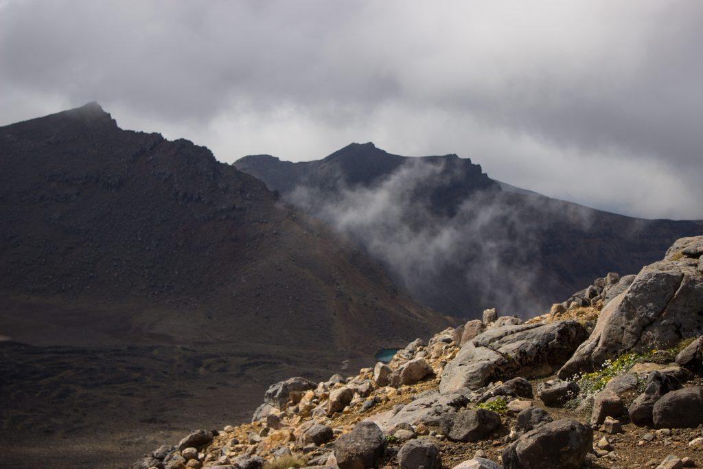 Tongariro Alpine Crossing Wanderung, Vulkanlandschaft, lebensfeindliche Landschaft, in Wolken gehüllte Berge, Geröll und Steine, Berggipfel in der Ferne, tolle Wanderung auf Nordinsel Neuseelands