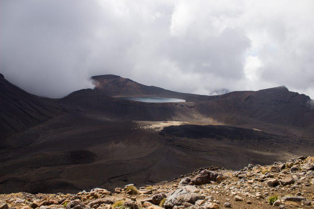 Tongariro Alpine Crossing Wanderung, Nordinsel Neuseeland, Vulkanlandschaft, lebensfeindliche Landschaft, in Wolken gehüllte Berge, Geröll und Steine, Aussicht auf Bergsee in Ferne