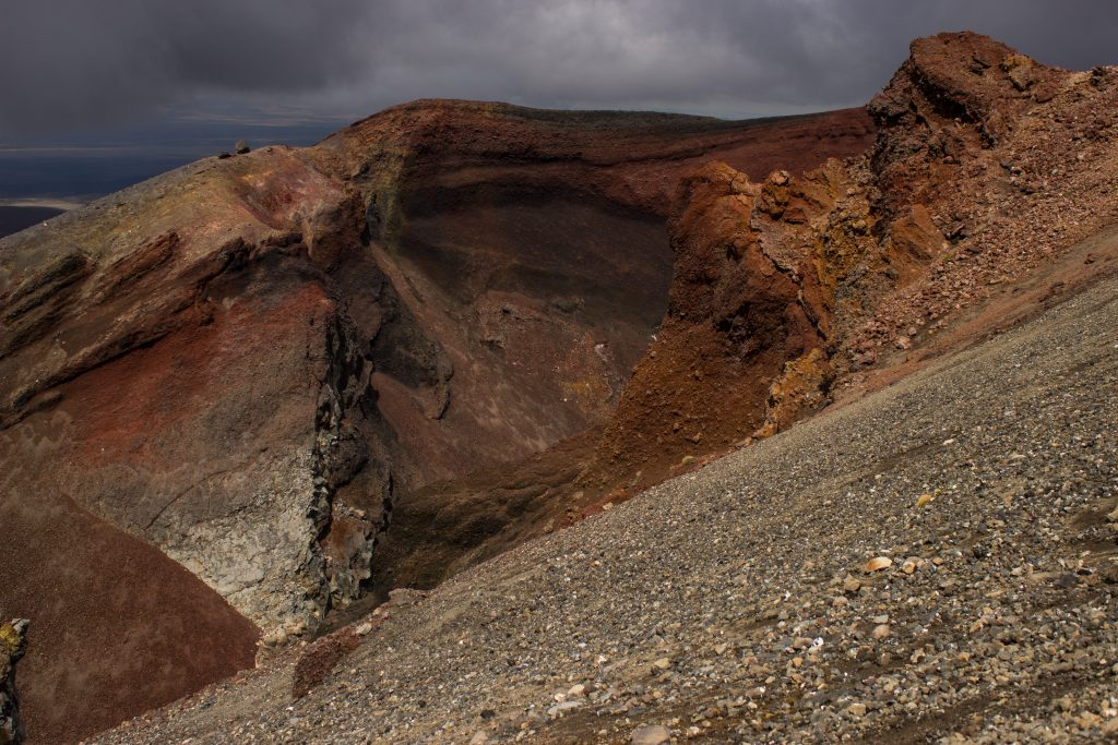 Tongariro Alpine Crossing Wanderung, Nordinsel Neuseeland, Vulkanlandschaft, lebensfeindliche Landschaft, in Wolken gehüllte Berge, Geröll und Steine, rote Vulkanasche, Red Crater