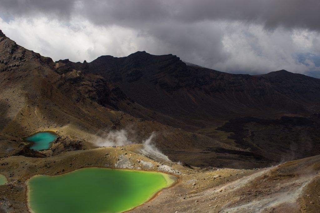 Tongariro Alpine Crossing Wanderung, Nordinsel Neuseeland, grüne Emerald Lakes, Vulkanlandschaft, lebensfeindliche Landschaft, in Wolken gehüllte Berge, Geröll und Steine