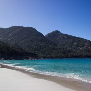 Wineglass Bay, Bucht im traumhaften Freycinet Nationalpark in Tasmanien, saftig grüner Wald, Berge, Strand mit schneeweißem Zuckersand und kristallklarem Wasser, Traumstrand