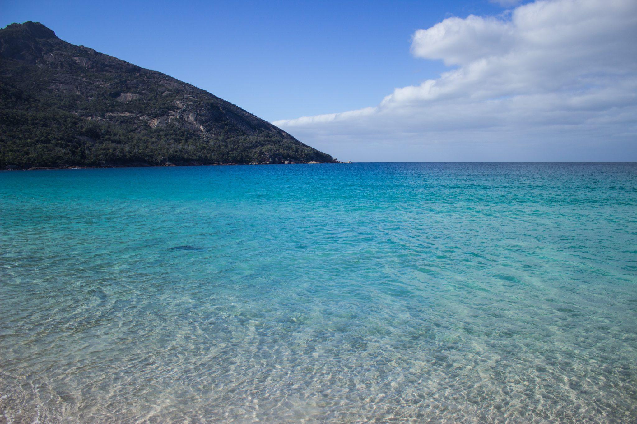 Wineglass Bay, Bucht im traumhaften Freycinet Nationalpark in Tasmanien, saftig grüner Wald, Strand mit schneeweißem Zuckersand und kristallklarem Wasser, Traumstrand