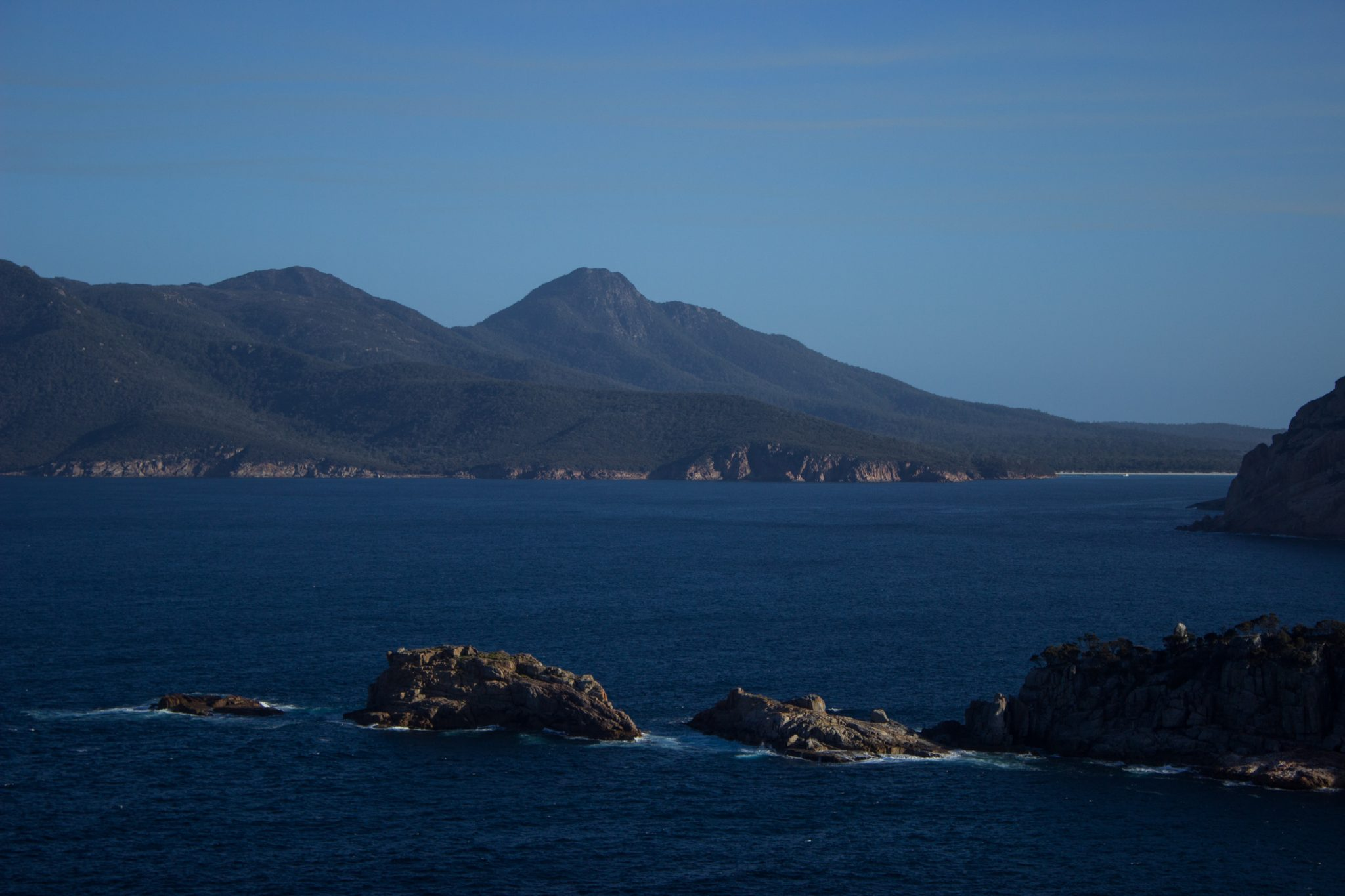 im traumhaften Freycinet Nationalpark in Tasmanien, saftig grüner Wald, Berge in der Ferne, wunderschönes Meer Ozean, Wellen