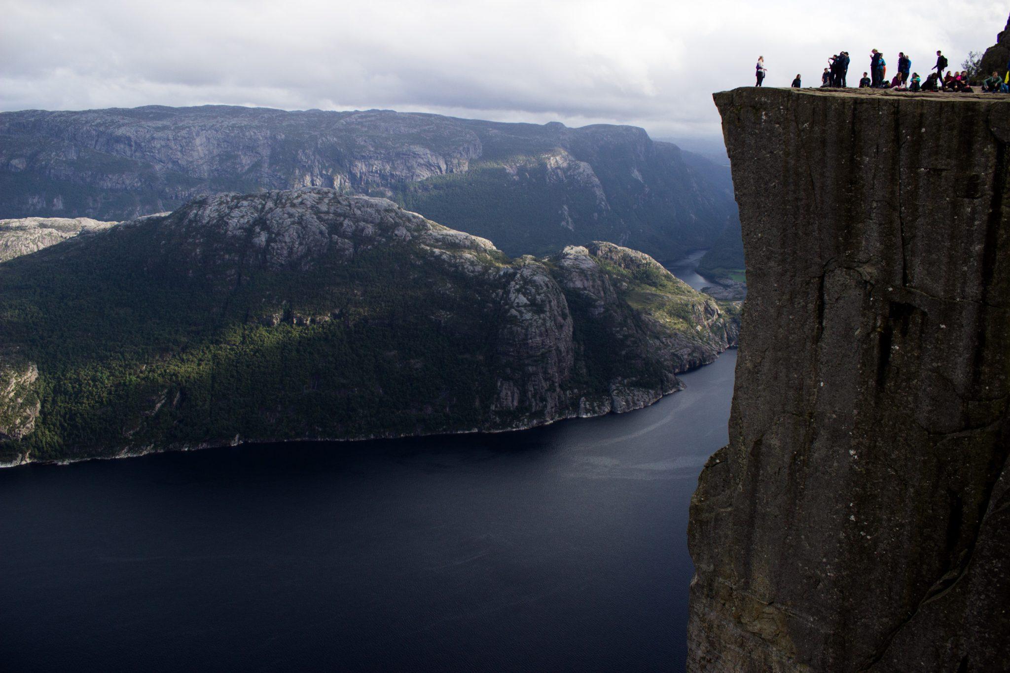 Wanderung zum Pulpit Rock Preikestolen, berühmtester Felsen in Norwegen, Blick auf Pulpit Rock, riesige steile Felswand mit Wanderern, 600 Meter darunter Lysefjord, traumhafte Landschaft