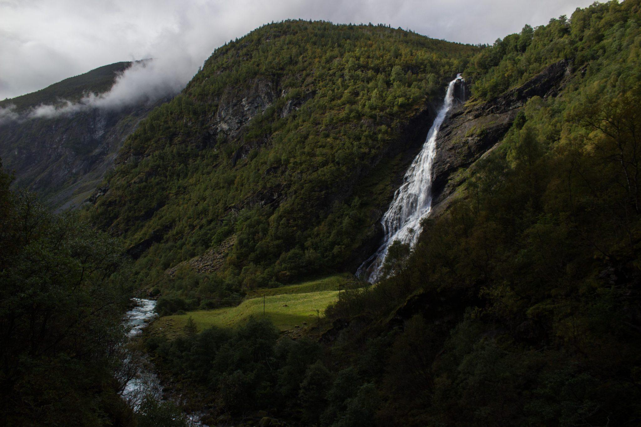 Wanderung zum Vettisfossen Wasserfall, höchster unregulierter Wasserfall in Norwegen, Blick von Brücke auf kleineren Wasserfall und sehr klares Wasser im Fluß und schönen Wald umringt von Bergen