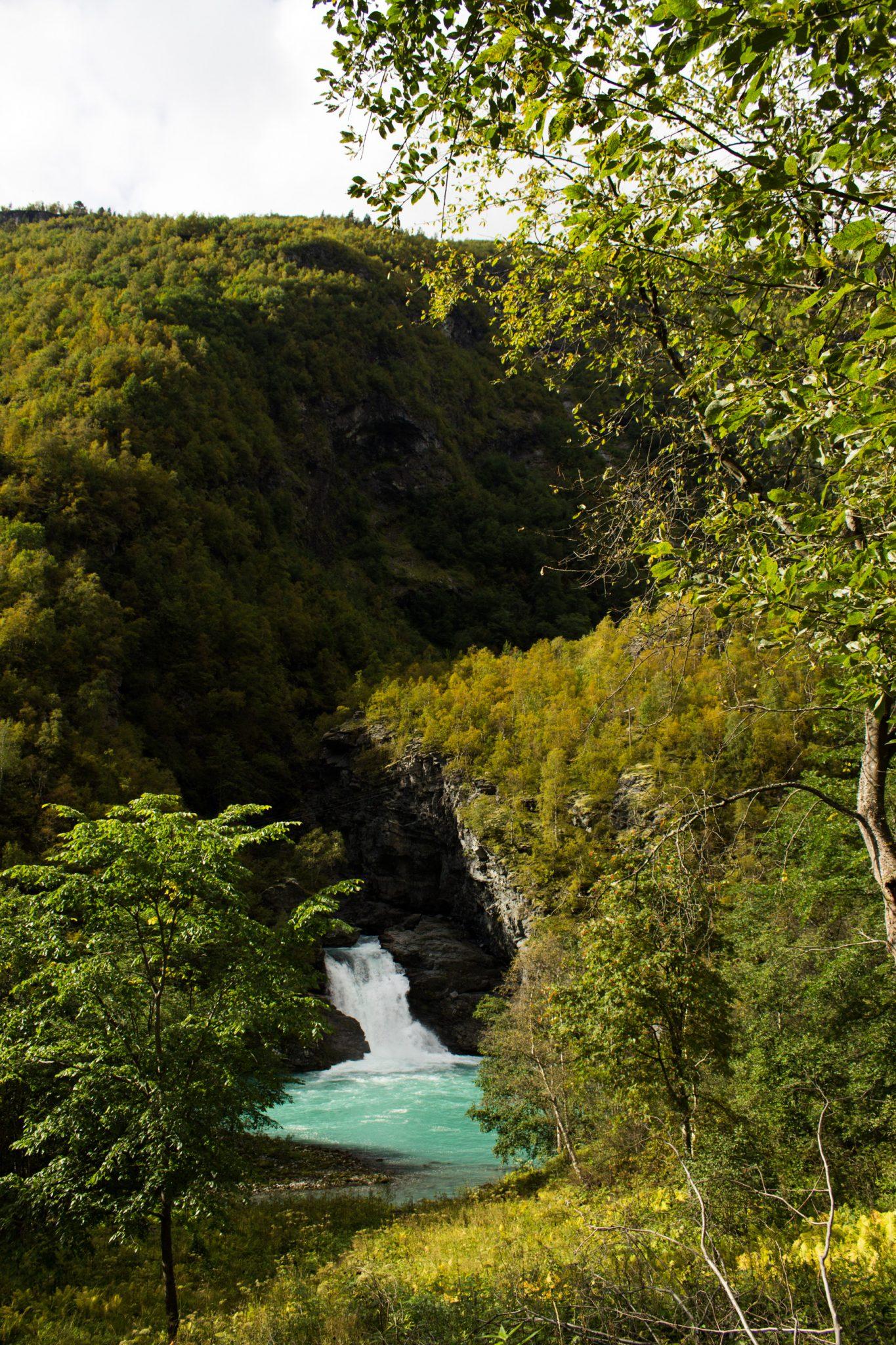 Wanderung zum Vettisfossen Wasserfall, höchster unregulierter Wasserfall in Norwegen, Blick von Brücke auf sehr klares Wasser im Fluß und schönen Wald umringt von Bergen, Sonne zaubert schönes Licht