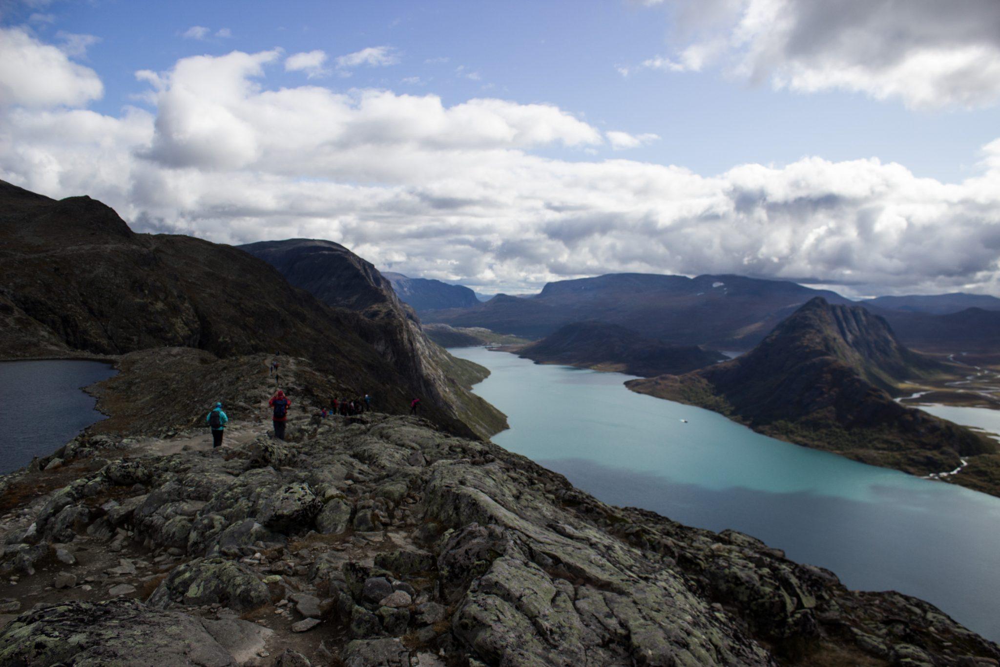Wanderung Besseggen-Grat im Jotunheimen Nationalpark, Aussicht auf wunderschönen Gjendesee und umgebende Berge, Blick auf Wanderweg Besseggen mit Wanderern