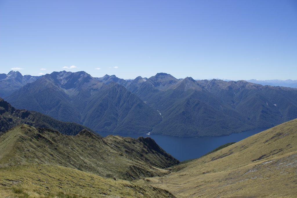 Wanderung Kepler Track - Great Walk, Wanderweg entlang Bergkamm im rauen Gelände, alpin oberhalb Baumgrenze, herrliche Aussicht, dunkelblauer See, herrlicher Sommertag in Neuseeland Südinsel, Fiordland National Park, Wandertag beim Kepler Track