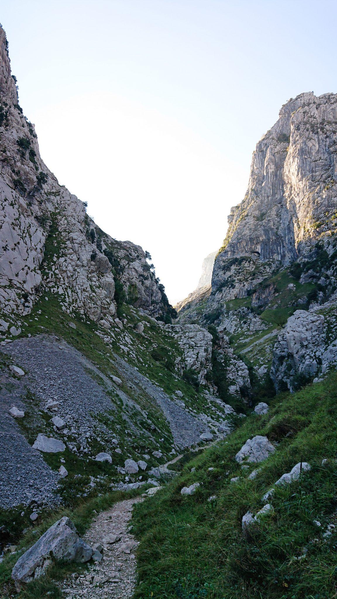 Wanderung Poncebos nach Bulnes in den Picos de Europa, schmaler Wanderpfad zwischen hohen Felswänden, saftig grüne Wiese, Steine und Geröll