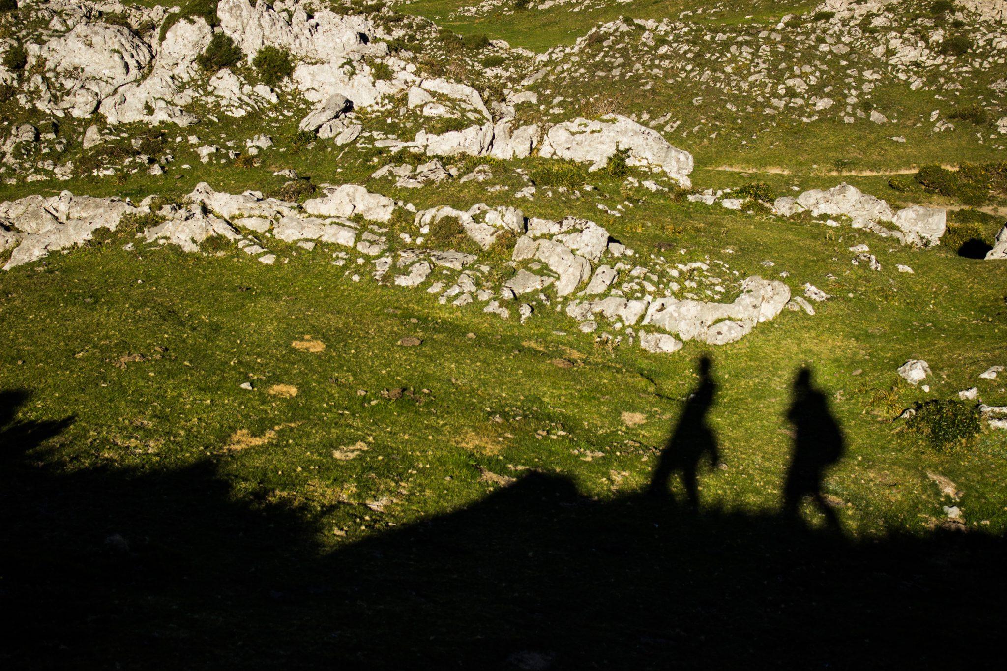 Wanderung Mirador de Ordiales Picos de Europa Spanien, schöner sehr schmaler und einsamer Wanderweg in Bergregion, Schatten von Wanderern Felsen und zerklüftete Steine, saftig grüne Wiesen, Nationalpark im Norden Spaniens