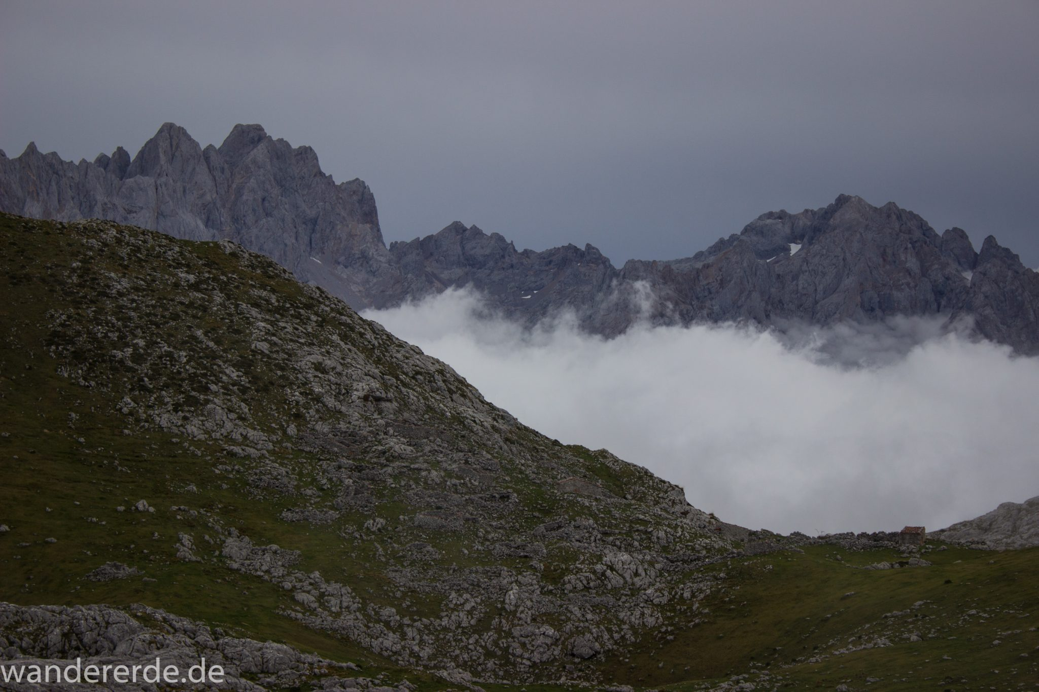 Wanderung Vega de Ario Picos de Europa Spanien, dichte Wolken, Bergregion in Nordspanien, Wandern, zerklüftete Felsen, Steine, schmaler Wanderpfad, atmosphärisch, Aussicht auf große Bergkette, grüne Wiese