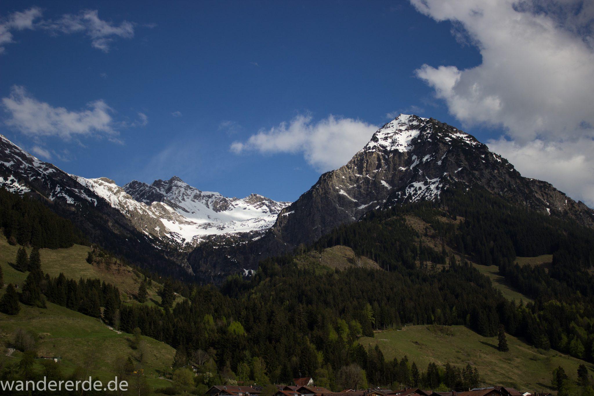 Wanderung Unterer Gaisalpsee, Abschnitt des Wanderwegs von Oberstdorf nach Fischen im Allgäu, Frühling im Allgäu, saftig grüne Wiesen und Wälder, Blick auf Berge mit schneebedeckten Gipfeln