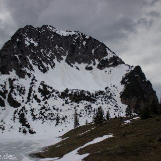 Wanderung Unterer Gaisalpsee, Wanderweg von Oberstdorf im Allgäu, Wanderpfad wird zunehmend schmaler, steil und felsig, weniger Bäume, Blick auf Allgäuer Berge mit Schnee und Unterer Gaisalpsee fast vollständig mit Eis und Schnee bedeckt, Wanderung zu Oberer Gaisalpsee nicht möglich Mitte Mai