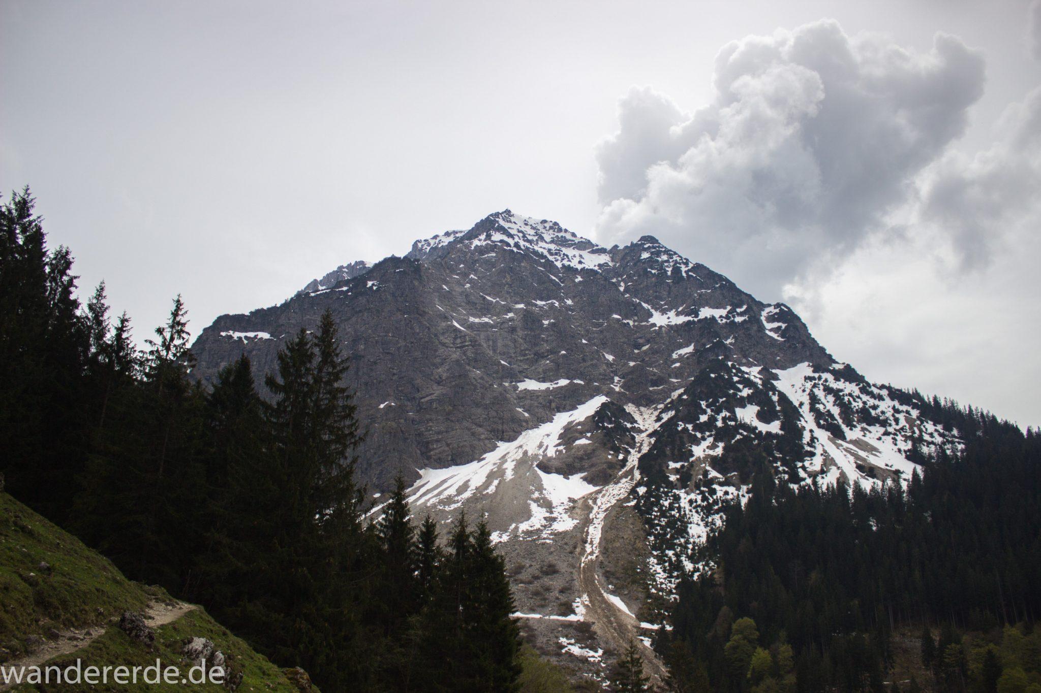 Wanderung Unterer Gaisalpsee, Wanderweg von Oberstdorf im Allgäu, Wanderpfad wird zunehmend schmaler, steil und felsig, umgeben von schönem dichtem Mischwald, Blick auf Allgäuer Berge mit Schnee in der Ferne