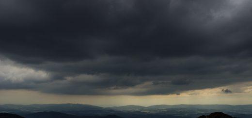 Rundwanderung zum Großen Arber im Bayerischen Wald, weite Aussicht auf riesiges Waldgebiet des bayerischen Waldes vom Berg Großer Arber, schöner und dichter Wald, Mischwald aus Laub- und Nadelbäume, Frühjahr im bayerischen Wald, sehr stimmungsvolles Licht durch dunkle Wolken und späten Tag