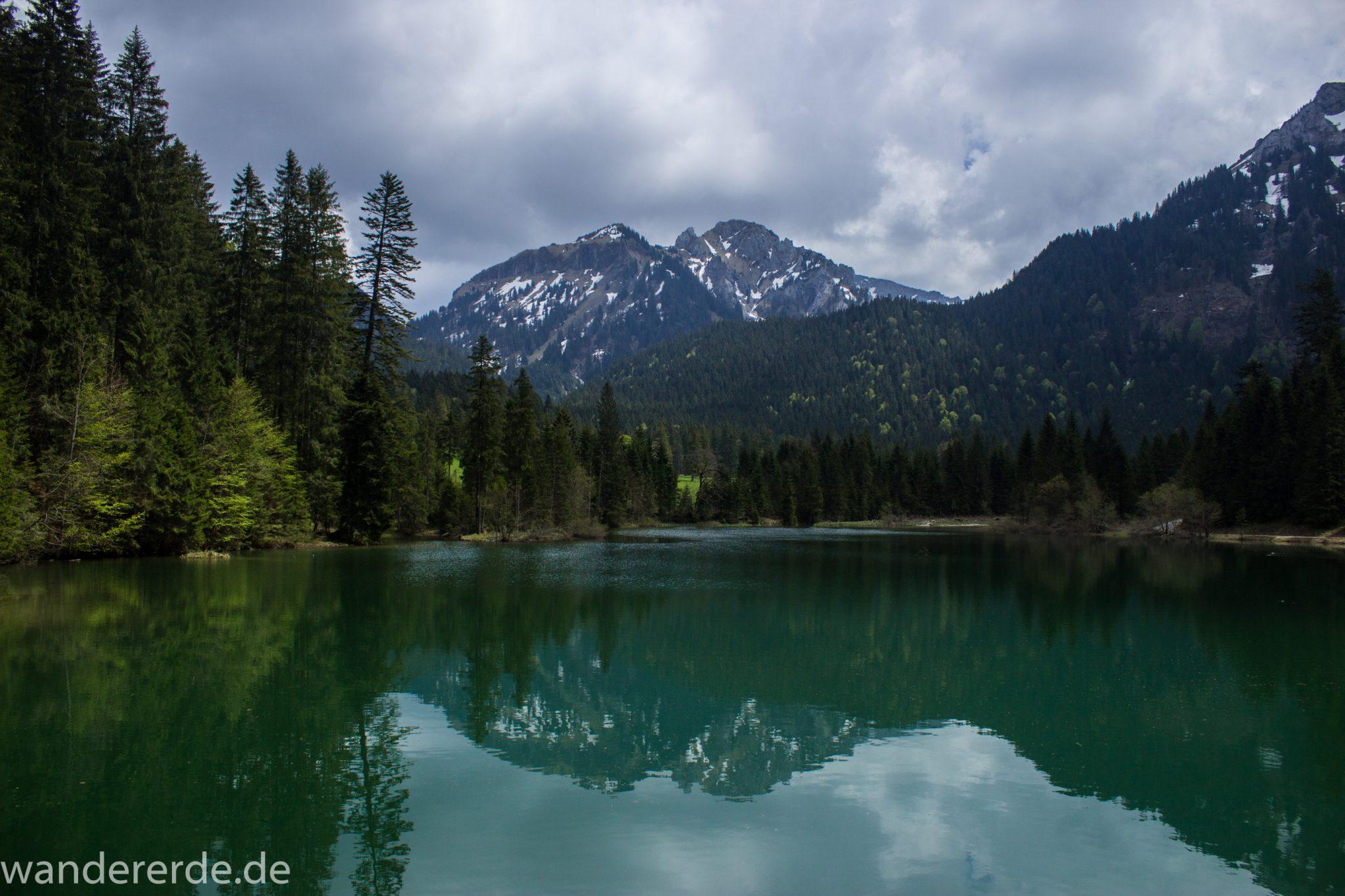 Wanderung zur Kenzenhütte in den Ammergauer Alpen, Aussicht beim Bockstallsee auf die Berge, teils schneebedeckte Gipfel in Wolken gehüllt, Frühjahr in den bayerischen Alpen, dichter grüner Wald umgibt den Bockstallsee