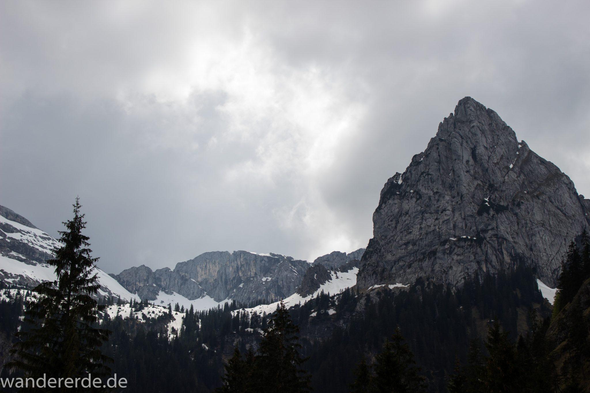 Wanderung zur Kenzenhütte in den Ammergauer Alpen, Aussicht auf die teils schneebedeckten Berge, spitzer Gipfel, Frühjahr in den bayerischen Alpen, sehr atmosphärisch durch dichte Wolkenfelder