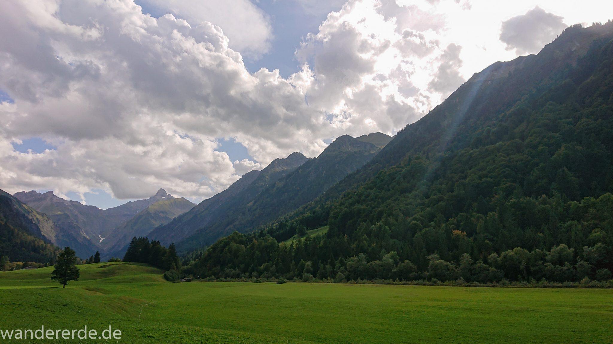 Alpenüberquerung Fernwanderweg E5 Oberstdorf Meran, 1. Etappe von Oberstdorf zur Kemptner Hütte, Wanderweg von Oberstdorf zur Spielmannsau führt entlang saftig grüner Wiesen im Allgäu umgeben von grünem Wald, Aussicht auf die Berge im Allgäu