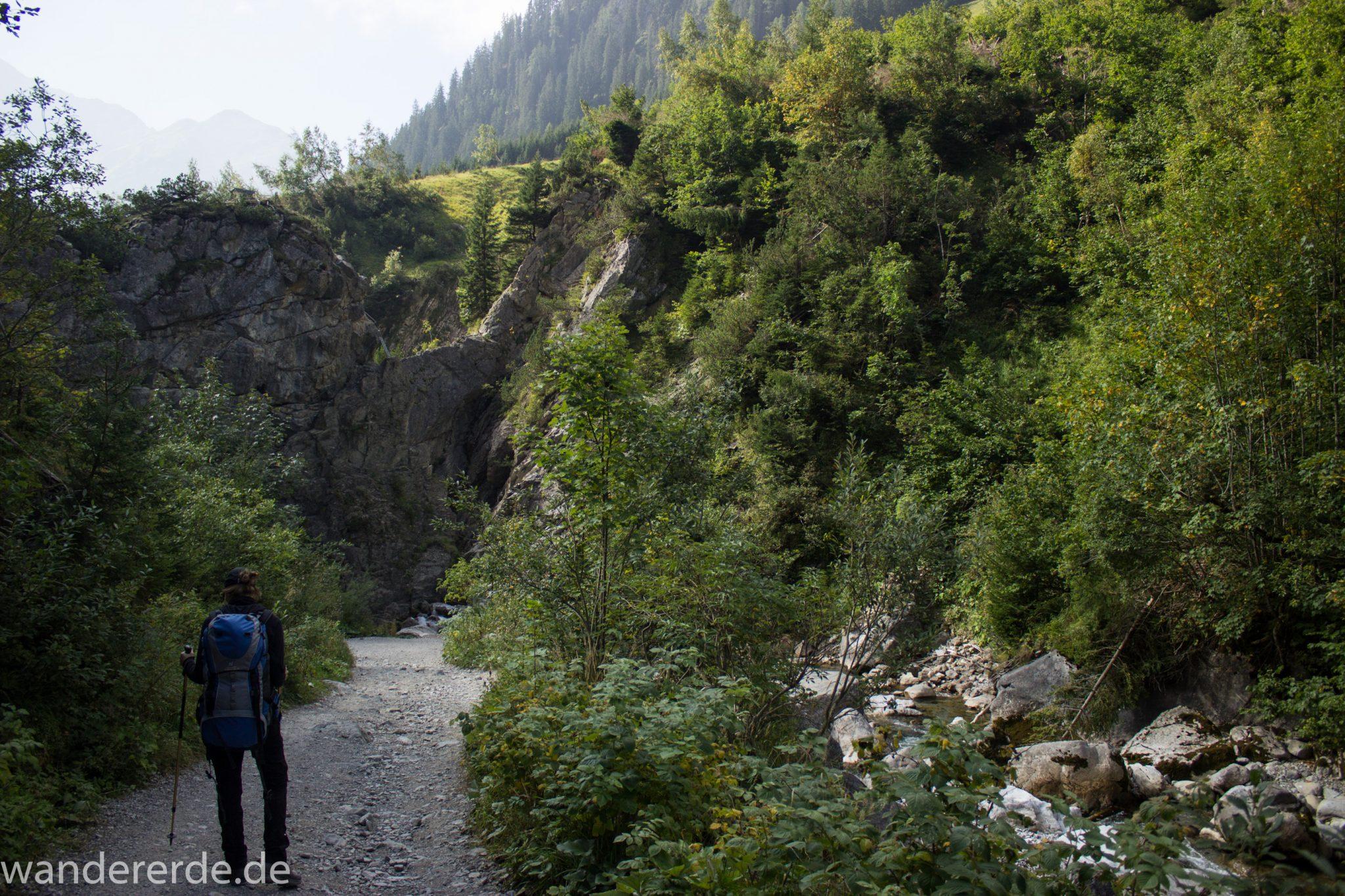 Alpenüberquerung Fernwanderweg E5 Oberstdorf Meran, 2. Etappe von Kemptner Hütte zur Memminger Hütte, Wanderer unterwegs auf schönem und abwechslungsreichem Wanderweg, Wanderpfad führt absteigend über die Obere und Untere Rossgumpenalpe in das sehr schöne Höhenbachtal mit beeindruckender Landschaft, grüne Vegetation mit Bäumen und Wiesen, idyllischer Rossgumpenbach fließt durch wolkenverhangenes Tal