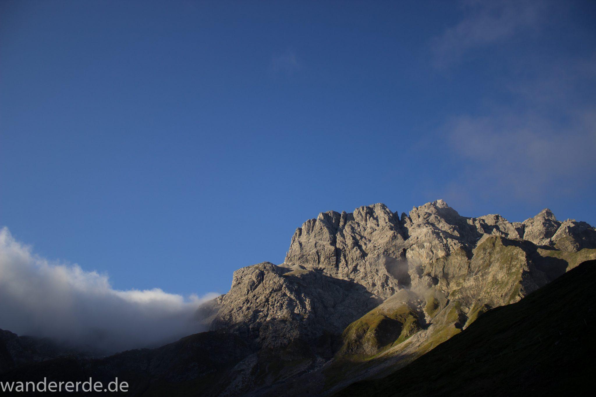 Alpenüberquerung Fernwanderweg E5 Oberstdorf Meran, 2. Etappe von Kemptner Hütte zur Memminger Hütte, kurz nach Sonnenaufgang in den Alpen bei der Kemptner Hütte, beeindruckende Berglandschaft wird in Sonnenlicht getaucht, Aussicht auf schöne Bergkette, Nebelfelder ziehen ab