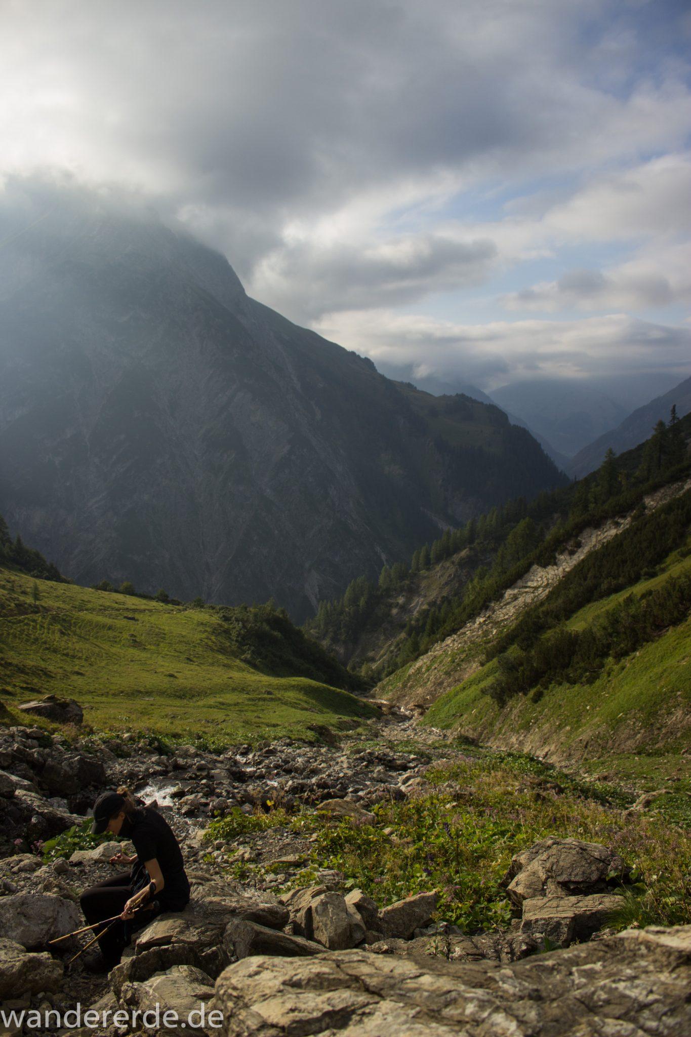 Alpenüberquerung Fernwanderweg E5 Oberstdorf Meran, 2. Etappe von Kemptner Hütte zur Memminger Hütte, schöner abwechslungsreicher und schmaler Wanderweg führt über Stock und Stein ab der Materialseilbahn der Memminger Hütte zunächst mäßig, dann steiler bergauf zur Memminger Hütte, idyllische Landschaft öffnet sich zu flacherer Ebene mit saftig grünen Wiesen und führt zum schönen Wasserfall umgeben von beeindruckenden Bergen und rundum schöner Aussicht, Wanderer macht Pause beim Wasserfall