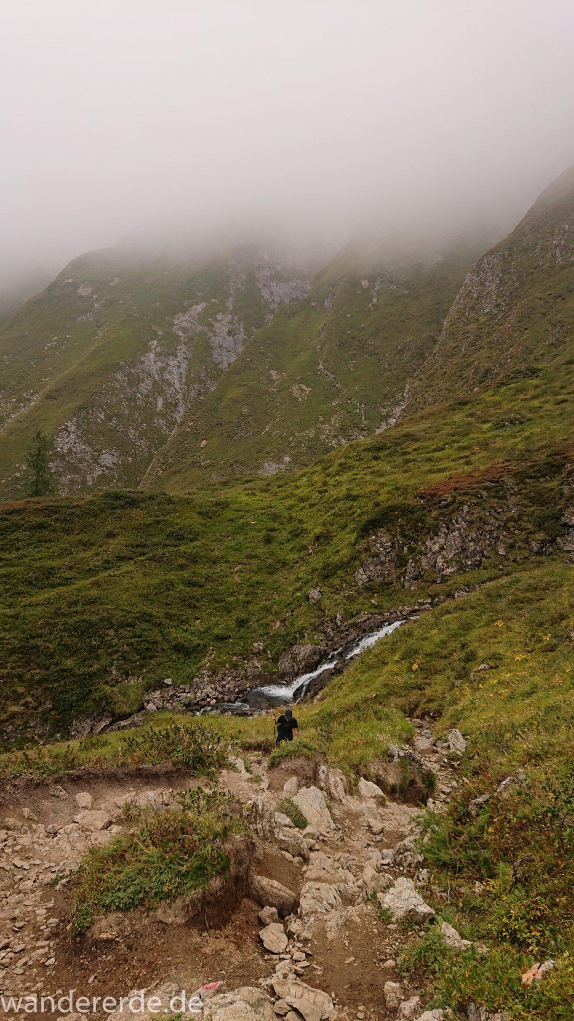 Alpenüberquerung Fernwanderweg E5 Oberstdorf Meran, 2. Etappe von Kemptner Hütte zur Memminger Hütte, schöner abwechslungsreicher und schmaler Wanderweg führt über Stock und Stein ab der Materialseilbahn der Memminger Hütte zunächst mäßig, dann steiler bergauf zur Memminger Hütte, ab schönem Wasserfall wird Wegverlauf steiler, umgeben von beeindruckenden Bergen und rundum schöner Aussicht, am späteren Nachmittag werden Berge langsam von aufziehenden Wolken verhangen, Wanderer nimmt steilen Anstieg in Angriff
