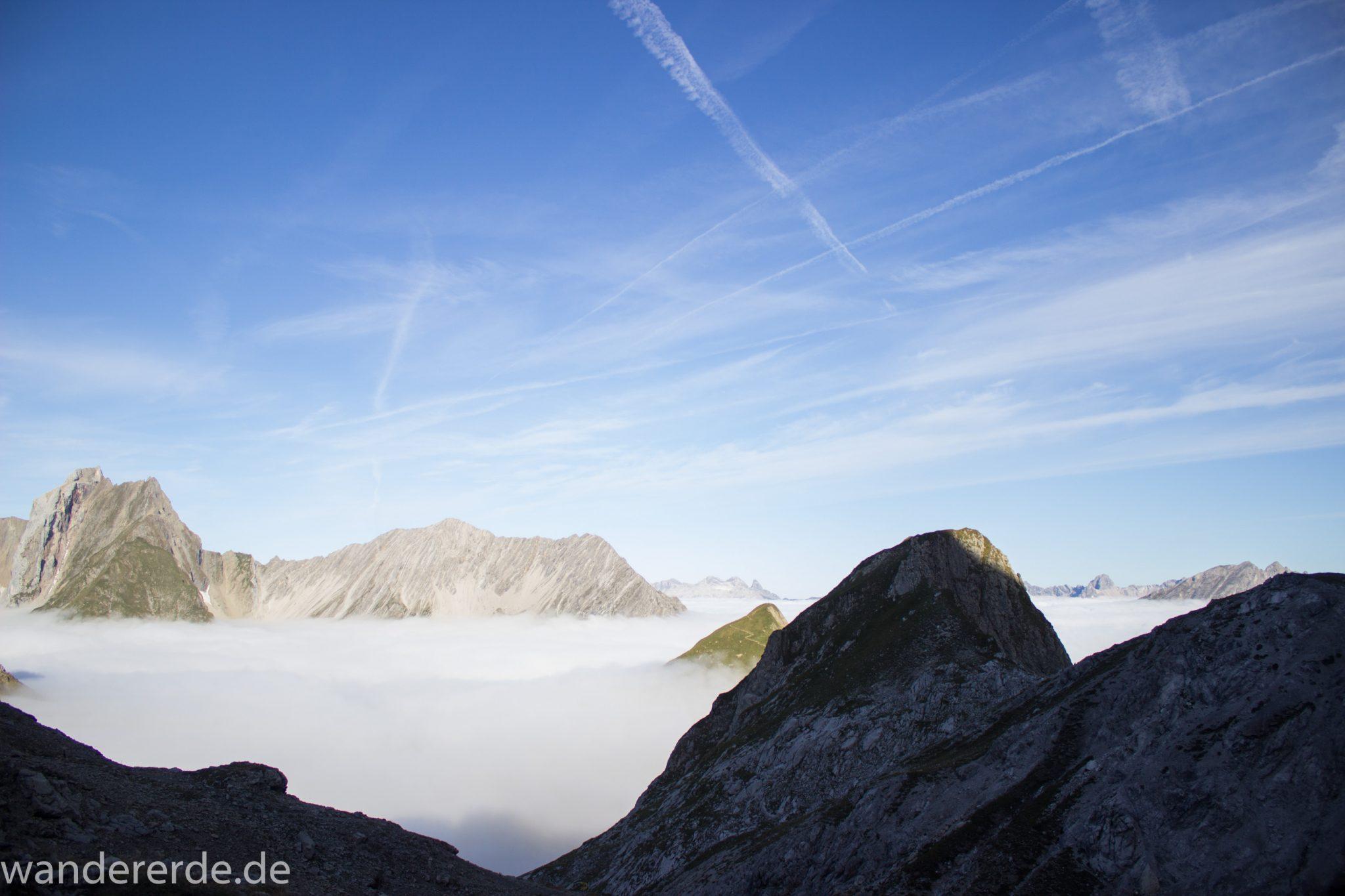 Alpenüberquerung Fernwanderweg E5 Oberstdorf Meran, 3. Etappe von Memminger Hütte zur Skihütte Zams, Berge sind am frühen Morgen noch in Nebel getaucht, aber die Sonne scheint, herrliches Wetter zum Wandern, E5 Wanderweg führt zu Beginn der dritten Etappe ab der Memminger Hütte über steilen und ausgesetzten Wanderweg über die Seescharte, ringsum Aussicht auf Berge der Alpen