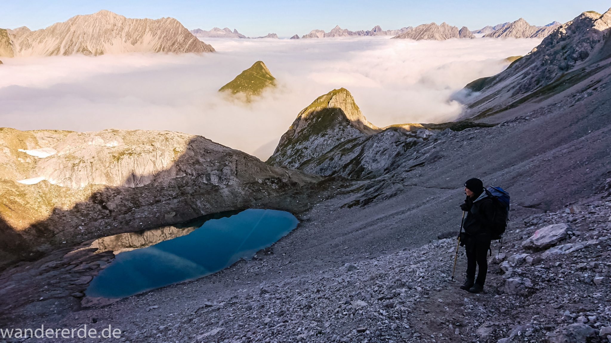 Alpenüberquerung Fernwanderweg E5 Oberstdorf Meran, 3. Etappe von Memminger Hütte zur Skihütte Zams, E5 Wanderweg führt zu Beginn der dritten Etappe ab der Memminger Hütte über steilen und ausgesetzten Wanderweg über die Seescharte, Wanderer blickt auf kristallklaren Bergsee während Aufstieg zur Seescharte auf sehr schmalen Wanderweg über viel Geröll, Aussicht auf Berge der Alpen die in Nebel gehüllt sind