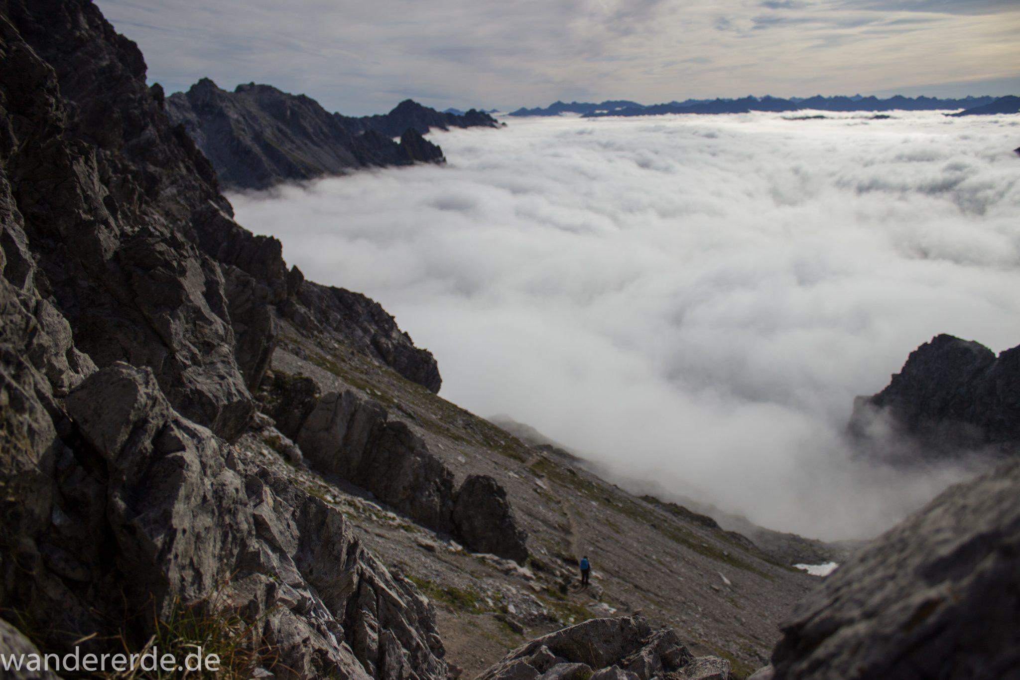 Alpenüberquerung Fernwanderweg E5 Oberstdorf Meran, 3. Etappe von Memminger Hütte zur Skihütte Zams, E5 Wanderweg führt zu Beginn der dritten Etappe ab der Memminger Hütte über steilen und ausgesetzten Wanderweg über die Seescharte, Blick auf die vor einem liegenden Berge der Alpen bei Erreichen der Seescharte, nach langem, steilen Aufstieg auf der schattigen Seite erreicht man damit die sonnige Seite und somit den Beginn eines lange währenden Abstiegs, Blick auf Wanderer der von der Seescharte absteigt Richtung Zams ins Lochbachtal