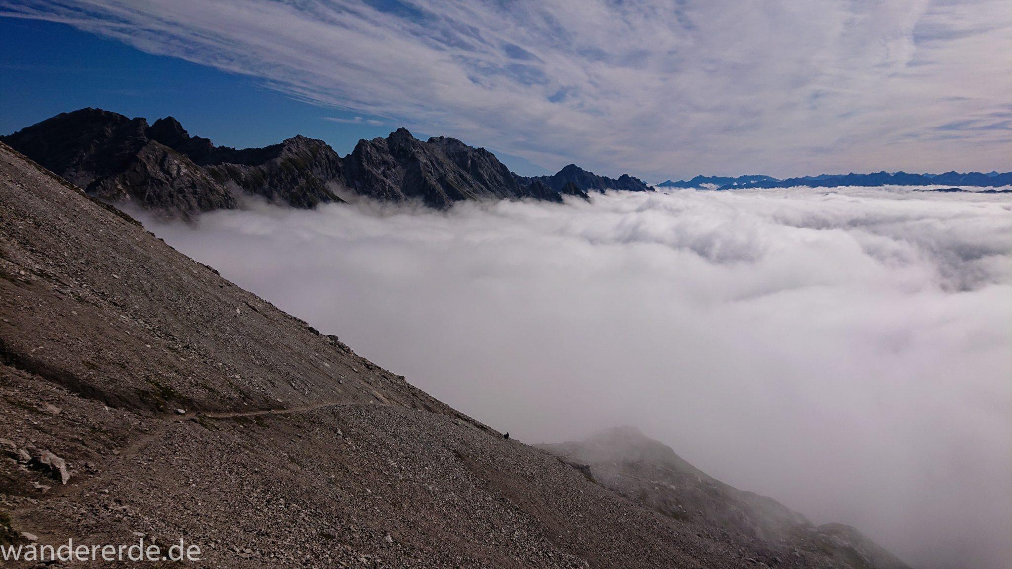 Alpenüberquerung Fernwanderweg E5 Oberstdorf Meran, 3. Etappe von Memminger Hütte zur Skihütte Zams, Blick auf die vor einem liegenden Berge der Alpen bei Erreichen der Seescharte, nach langem, steilen Aufstieg auf der schattigen Seite erreicht man damit die sonnige Seite und somit den Beginn eines lange währenden Abstiegs, Blick auf schmalen Wanderpfad mit viel Geröll während Abstieg ins Lochbachtal Richtung Zams, Berge liegen im Nebel verborgen