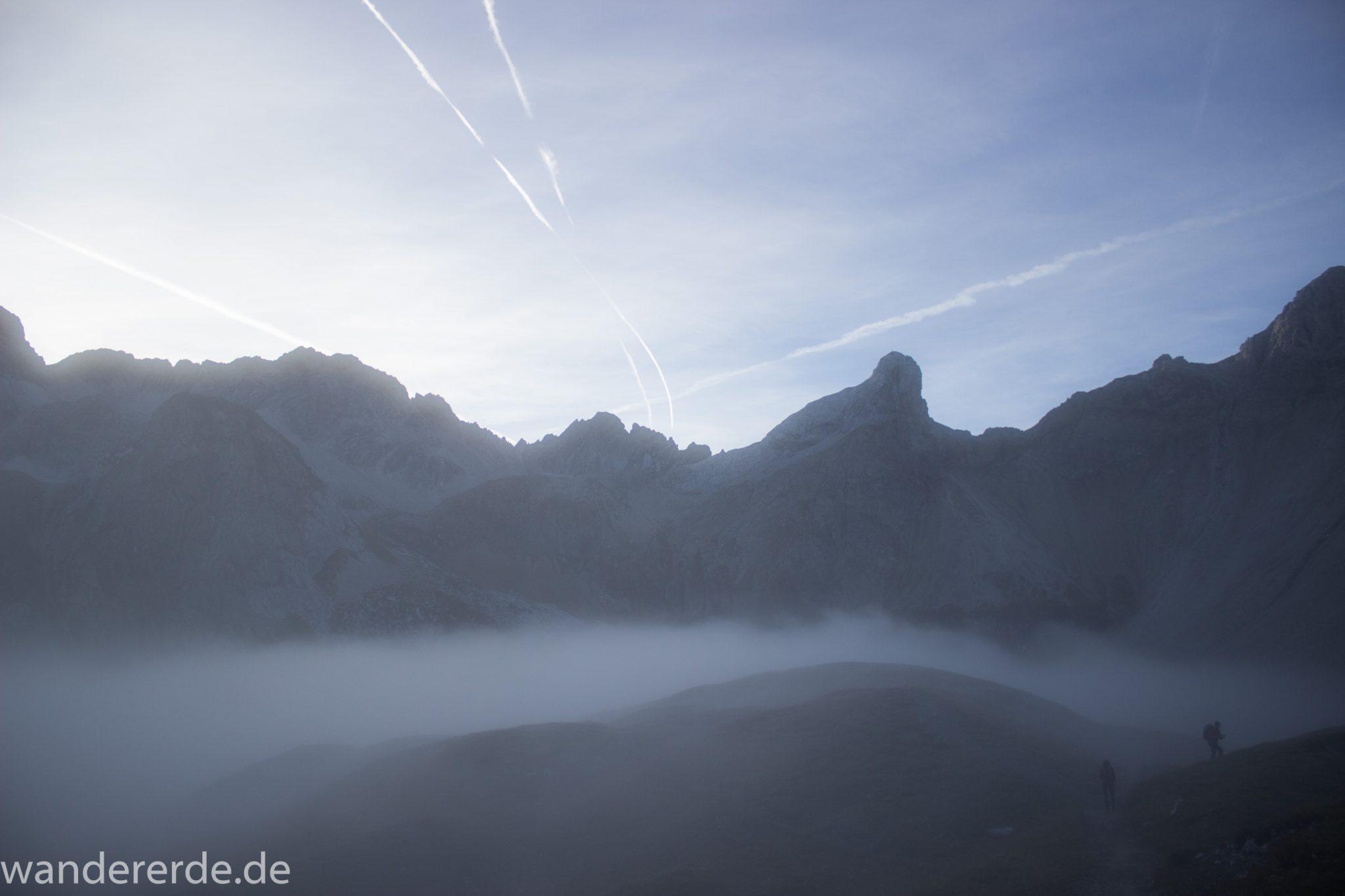 Alpenüberquerung Fernwanderweg E5 Oberstdorf Meran, 3. Etappe von Memminger Hütte zur Skihütte Zams, Berge sind am frühen Morgen noch in Nebel getaucht, aber die Sonne scheint, herrliches Wetter zum Wandern, E5 Wanderweg führt zu Beginn der dritten Etappe ab der Memminger Hütte über steilen und ausgesetzten Wanderweg über die Seescharte, Blick auf Wanderer im Nebel