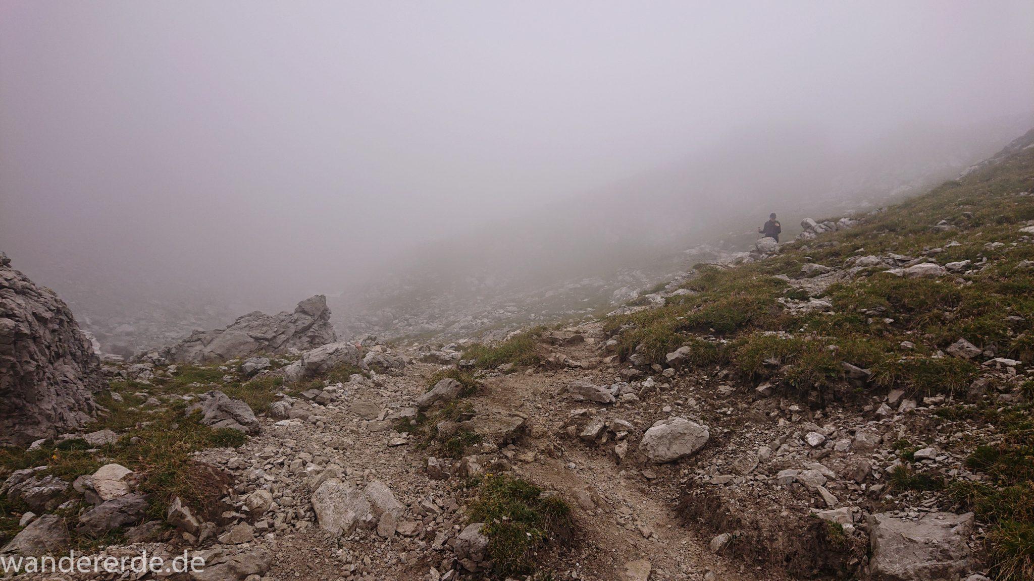 Alpenüberquerung Fernwanderweg E5 Oberstdorf Meran, 3. Etappe von Memminger Hütte zur Skihütte Zams, nach Erreichen der Seescharte folgt ein sehr langer Abstieg ins Lochbachtal Richtung Zams, Blick auf Wanderer unterwegs auf schmalem Wanderpfad mit viel Geröll, Berge und Umgebung liegen im Nebel verborgen