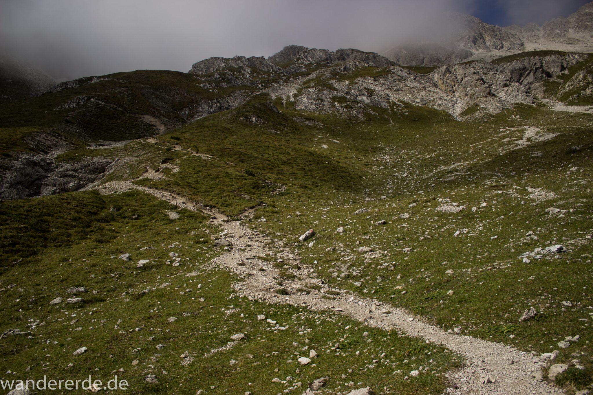 Alpenüberquerung Fernwanderweg E5 Oberstdorf Meran, 3. Etappe von Memminger Hütte zur Skihütte Zams, nach Erreichen der Seescharte folgt ein sehr langer Abstieg ins Lochbachtal Richtung Zams, Aussicht auf Berge und Bergwiesen, Berge und Umgebung liegen teils im Nebel verborgen, Blick auf schmalen Wanderpfad mit viel Geröll
