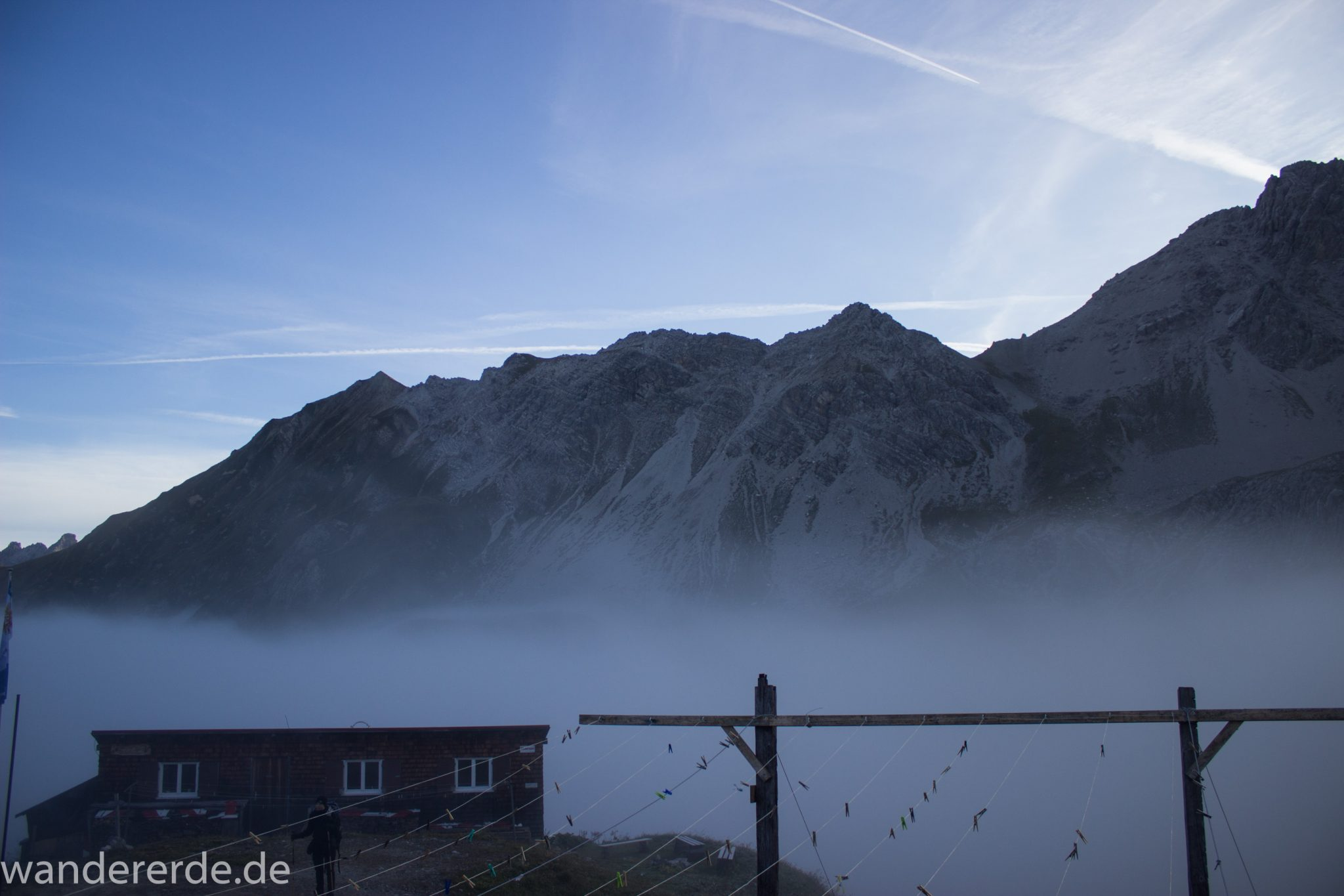 Alpenüberquerung Fernwanderweg E5 Oberstdorf Meran, 3. Etappe von Memminger Hütte zur Skihütte Zams, Berge sind am frühen Morgen noch in Nebel getaucht, aber die Sonne scheint, herrliches Wetter zum Wandern, Blick auf Nebengebäude der Memmimger Hütte, Wanderer steht davor
