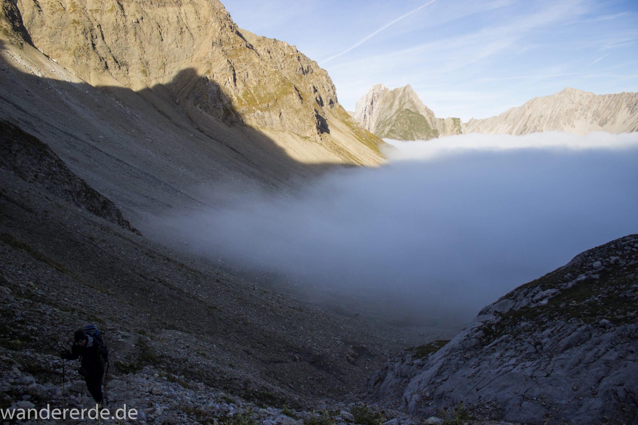 Alpenüberquerung Fernwanderweg E5 Oberstdorf Meran, 3. Etappe von Memminger Hütte zur Skihütte Zams, Berge sind am frühen Morgen noch in Nebel getaucht, aber die Sonne scheint, herrliches Wetter zum Wandern, E5 Wanderweg führt zu Beginn der dritten Etappe ab der Memminger Hütte über steilen und ausgesetzten Wanderweg über die Seescharte, Blick auf Wanderer während Aufstieg zur Seescharte auf sehr schmalem Wanderweg über viel Geröll, ringsum Aussicht auf Berge der Alpen