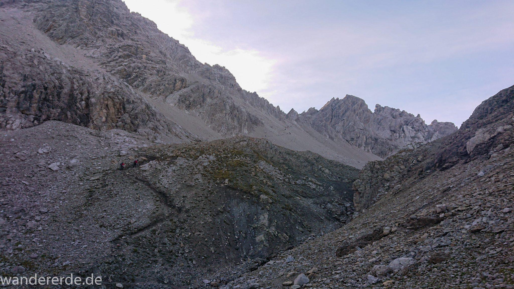 Alpenüberquerung Fernwanderweg E5 Oberstdorf Meran, 3. Etappe von Memminger Hütte zur Skihütte Zams, E5 Wanderweg führt zu Beginn der dritten Etappe ab der Memminger Hütte über steilen und ausgesetzten Wanderweg über die Seescharte, Blick auf Wanderer während Aufstieg zur Seescharte auf sehr schmalem Wanderweg über viel Geröll, Aussicht auf Berge der Alpen