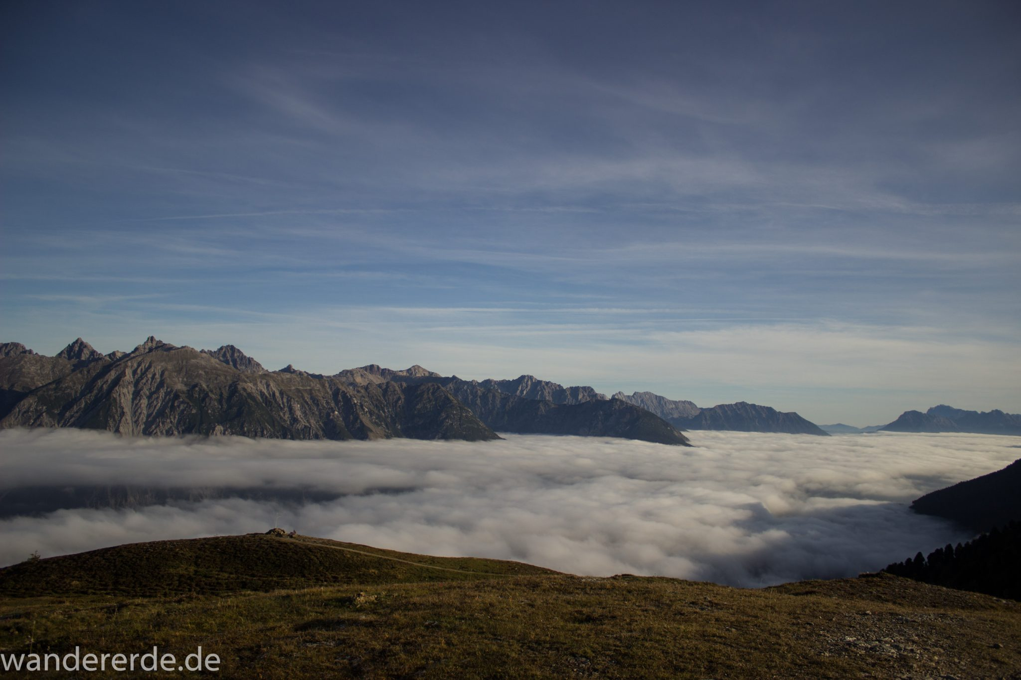 Alpenüberquerung Fernwanderweg E5 Oberstdorf Meran, 4. Etappe von Skihütte Zams zur Braunschweiger Hütte, Aussicht bei der Bergstation der Venet Bergbahn auf die Berge der Alpen, sind noch von Nebel umgeben, herrliches Wanderwetter bei strahlendem Sonnenschein