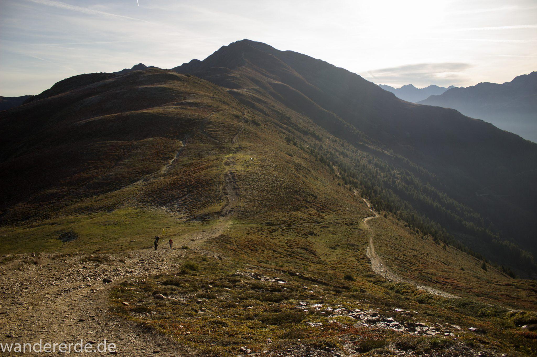 Alpenüberquerung Fernwanderweg E5 Oberstdorf Meran, 4. Etappe von Skihütte Zams zur Braunschweiger Hütte, Aussicht bei der Bergstation der Venet Bergbahn auf die Berge der Alpen, herrliches Wanderwetter bei strahlendem Sonnenschein, Wanderer sind auf schmalem Wanderweg unterwegs um über den Grat mit Kreuzjoch nach Wenns zu gehen, rechter Wanderweg Venetrundweg über Galfun Alm und Gogles Alm