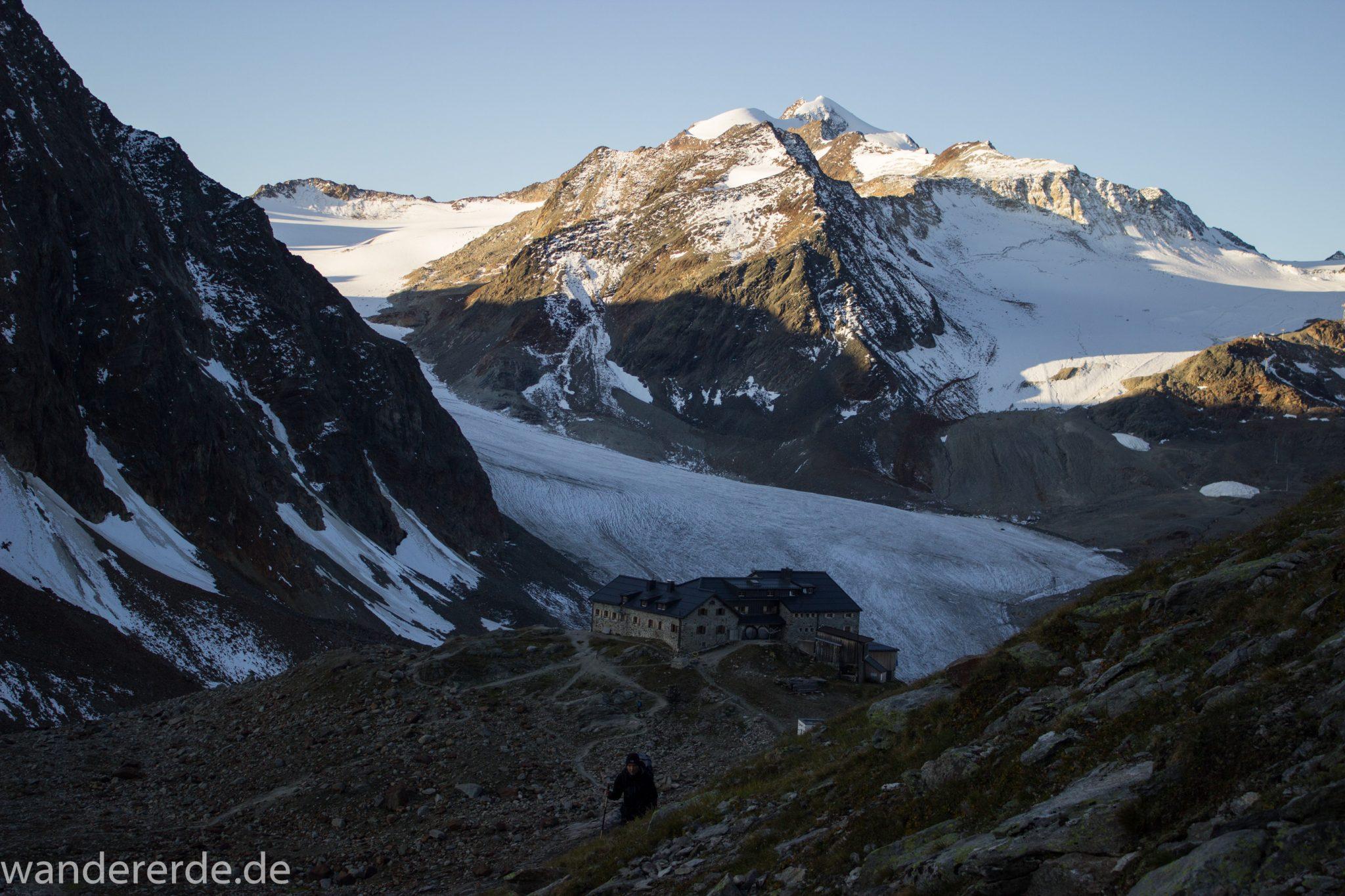 Alpenüberquerung Fernwanderweg E5 Oberstdorf Meran, 5. Etappe von Braunschweiger Hütte zur Martin-Busch-Hütte, zu Beginn der 5. Etappe Blick zurück auf die Braunschweiger Hütte und die umliegenden Berge der Alpen, Wanderer auf steilem und schmalem Wanderweg mit viel Geröll hinauf zum Pitztaler Jöchl, beeindruckende Berge türmen sich vor einem auf, Reste von Schneefeldern