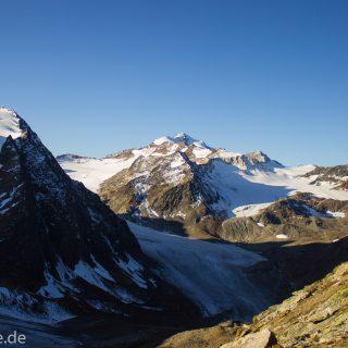 Alpenüberquerung Fernwanderweg E5 Oberstdorf Meran, 5. Etappe von Braunschweiger Hütte zur Martin-Busch-Hütte, zu Beginn der 5. Etappe steiler und schmaler Wanderweg mit viel Geröll hinauf zum Pitztaler Jöchl, Wanderer unterwegs auf Wanderpfad bei schönem Wetter, beeindruckende Berge umgeben einen, teils große Schneefelder in der Nähe der Gipfel