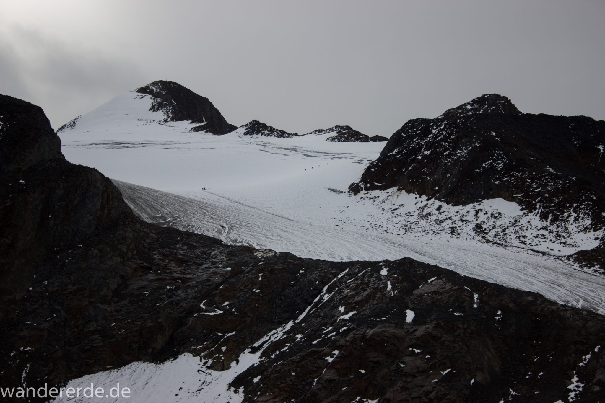 Alpenüberquerung Fernwanderweg E5 Oberstdorf Meran, 6. Etappe von Martin-Busch-Hütte nach Vernagt / Meran, die letzte Etappe der Alpenüberquerung auf dem E5 startet mit dem Aufstieg zur Similaun-Hütte, dem höchsten Punkt der gesamten Alpenüberquerung, umliegende sehr beeindruckende Bergwelt erscheint unwirklich und mystisch, Berghänge mit viel Geröll, Wanderweg verläuft steil bergauf, Blick auf Wanderer die zum Gipfel des Similaun Berges wandern über Schneefelder, nicht Teil des E5