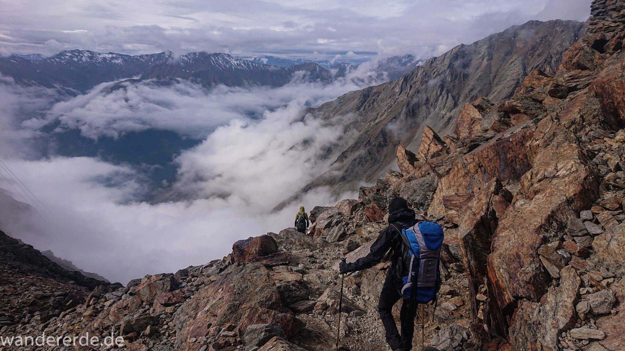 Alpenüberquerung Fernwanderweg E5 Oberstdorf Meran, 6. Etappe von Martin-Busch-Hütte nach Vernagt / Meran, die letzte Etappe der Alpenüberquerung auf dem E5 startet mit dem Aufstieg zur Similaun-Hütte, dem höchsten Punkt der gesamten Alpenüberquerung, umliegende sehr beeindruckende Bergwelt erscheint unwirklich und mystisch, Berghänge mit viel Geröll, Wanderweg verläuft nach der Similaun-Hütte steil abwärts Richtung Vernagt im Schnalstal, Wanderer während steilem Abstieg auf ausgesetztem Pfad